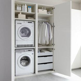 Ejemplo de lavadero lineal, actual, pequeño, con armarios con paneles lisos, puertas de armario blancas, paredes blancas y lavadora y secadora apiladas