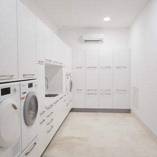 This is an example of a large contemporary l-shaped laundry room in Malaga with flat-panel cabinets, white cabinets, laminate benchtops, white splashback, ceramic splashback, porcelain floors, white walls, beige floor and a drop-in sink.