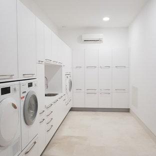 Bild på en stor funkis l-formad tvättstuga, med släta luckor, vita skåp, laminatbänkskiva, vitt stänkskydd, stänkskydd i keramik, klinkergolv i porslin, vita väggar, beiget golv och en nedsänkt diskho