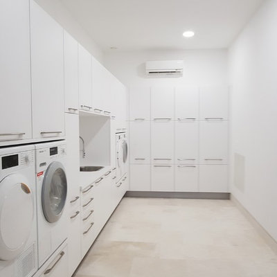 Large trendy l-shaped porcelain tile and beige floor laundry room photo in Malaga with flat-panel cabinets, white cabinets, laminate countertops, white backsplash, ceramic backsplash, white walls and a drop-in sink