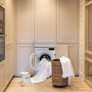 Inspiration för mellanstora moderna l-formade vitt små tvättstugor med garderob, med en undermonterad diskho, luckor med upphöjd panel, grå skåp, bänkskiva i kvarts, vitt stänkskydd, flerfärgade väggar, laminatgolv och brunt golv