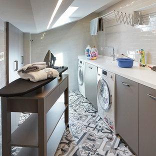 Cette photo montre une buanderie linéaire tendance dédiée avec un évier intégré, un placard à porte plane, des portes de placard grises, un mur blanc, des machines côte à côte, un sol multicolore et un plan de travail blanc.