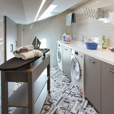 Inspiration for a contemporary single-wall multicolored floor dedicated laundry room remodel in Barcelona with an integrated sink, flat-panel cabinets, gray cabinets, white walls, a side-by-side washer/dryer and white countertops