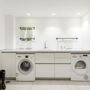 Foto de cuarto de lavado lineal, moderno, grande, con fregadero encastrado, armarios con paneles lisos, puertas de armario blancas, paredes blancas, lavadora y secadora juntas, suelo blanco y encimeras blancas
