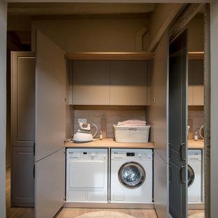 Bild på en liten vintage beige linjär beige liten tvättstuga, med släta luckor, en tvättmaskin och torktumlare bredvid varandra, träbänkskiva, ljust trägolv, beiget golv och grå skåp
