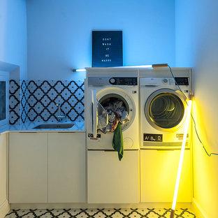 Eklektisk inredning av en liten linjär tvättstuga enbart för tvätt, med en undermonterad diskho, klinkergolv i keramik, släta luckor, vita skåp, bänkskiva i kvartsit, svarta väggar, en tvättpelare och flerfärgat golv