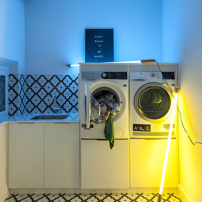 Dedicated laundry room - small eclectic single-wall ceramic tile and multicolored floor dedicated laundry room idea in Other with an undermount sink, flat-panel cabinets, white cabinets, quartzite countertops, black walls and a stacked washer/dryer