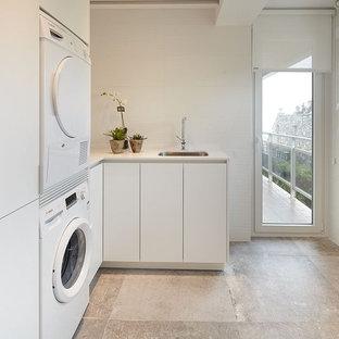 Foto de cuarto de lavado en L, contemporáneo, de tamaño medio, con fregadero de un seno, armarios con paneles lisos, puertas de armario blancas, paredes blancas y lavadora y secadora apiladas