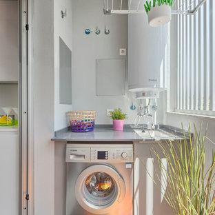 Foto de cuarto de lavado lineal, bohemio, de tamaño medio, con fregadero bajoencimera, armarios con paneles lisos, puertas de armario grises, paredes blancas y encimeras grises