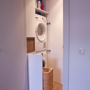 Foto på en liten funkis liten tvättstuga, med släta luckor, vita skåp, vita väggar, mellanmörkt trägolv och en tvättpelare