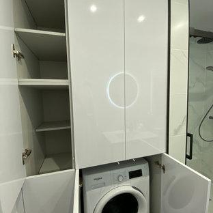 Exempel på en liten modern linjär liten tvättstuga med garderob, med släta luckor, vita skåp, vita väggar, klinkergolv i keramik och svart golv
