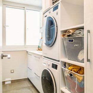 Foto de lavadero lineal, contemporáneo, con armarios con paneles lisos, puertas de armario blancas, paredes blancas, lavadora y secadora apiladas, suelo gris y encimeras blancas