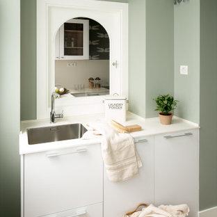Ejemplo de cuarto de lavado lineal, nórdico, de tamaño medio, con fregadero bajoencimera, armarios con paneles lisos, puertas de armario blancas, encimera de cuarzo compacto, paredes verdes, suelo laminado, lavadora y secadora escondidas y encimeras blancas