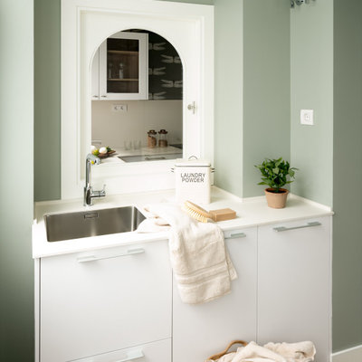 Dedicated laundry room - mid-sized scandinavian single-wall laminate floor dedicated laundry room idea in Bilbao with an undermount sink, flat-panel cabinets, white cabinets, quartz countertops, green walls, a concealed washer/dryer and white countertops