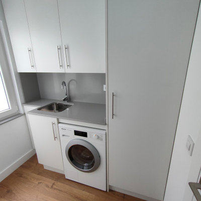 Dedicated laundry room - mid-sized transitional single-wall medium tone wood floor and brown floor dedicated laundry room idea in Other with an undermount sink, flat-panel cabinets, white cabinets, quartz countertops, white walls, an integrated washer/dryer and gray countertops