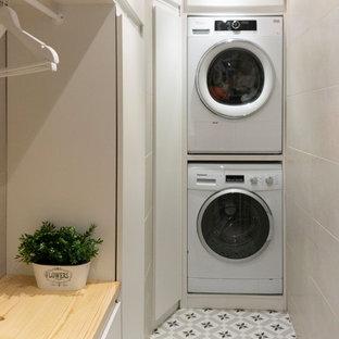 Modelo de lavadero multiusos y en L, bohemio, pequeño, con armarios abiertos, puertas de armario blancas, encimera de madera, paredes blancas, suelo de baldosas de cerámica, lavadora y secadora apiladas, suelo gris y encimeras marrones