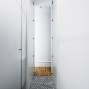 This is an example of a large classic single-wall utility room in Madrid with a submerged sink, recessed-panel cabinets, white cabinets, grey walls, ceramic flooring, a concealed washer and dryer and turquoise floors.