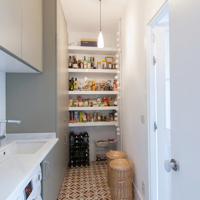 Utility room - mid-sized transitional single-wall ceramic tile utility room idea in Madrid with flat-panel cabinets, gray cabinets, marble countertops, white walls, a side-by-side washer/dryer and an undermount sink