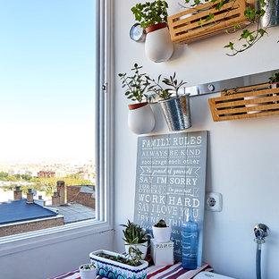 Cette photo montre une petit buanderie linéaire multi-usage avec un placard à porte plane, des portes de placard blanches, un plan de travail en stratifié, un mur blanc, un sol en carrelage de porcelaine, un sol gris et un plan de travail rouge.
