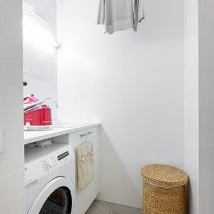 Diseño de cuarto de lavado lineal, contemporáneo, pequeño, con armarios con paneles lisos, puertas de armario blancas, encimera de laminado, paredes blancas, suelo de baldosas de cerámica, suelo gris, encimeras blancas y fregadero encastrado