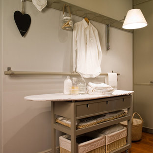 Inspiration for an eclectic laundry room in Barcelona with grey cabinets.