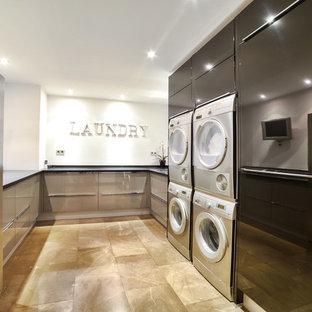 Ejemplo de cuarto de lavado en U, actual, con armarios con paneles lisos, puertas de armario grises, encimeras negras, paredes blancas, lavadora y secadora juntas y suelo beige