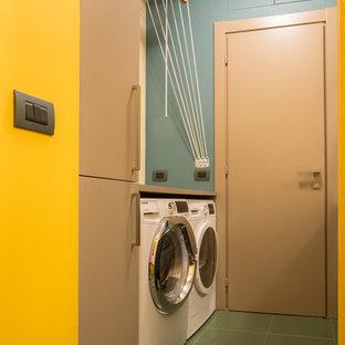 Immagine di una lavanderia contemporanea di medie dimensioni con pareti blu, lavatrice e asciugatrice affiancate e pavimento verde