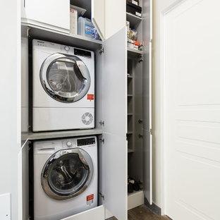 Inredning av en modern liten tvättstuga, med släta luckor, vita skåp, en tvättpelare, mörkt trägolv och brunt golv