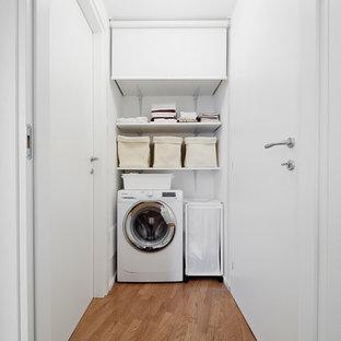 Idee per una sala lavanderia contemporanea con pareti bianche e pavimento in legno massello medio