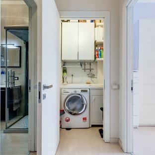 Esempio di una piccola lavanderia multiuso minimalista con ante lisce, ante bianche, pareti beige, pavimento in laminato, lavatrice e asciugatrice affiancate e pavimento beige