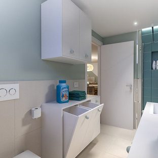 Photo of a small scandinavian single-wall utility room in Milan with a drop-in sink, flat-panel cabinets, white cabinets, laminate benchtops, beige splashback, porcelain splashback, green walls, porcelain floors, a side-by-side washer and dryer, beige floor, white benchtop and recessed.