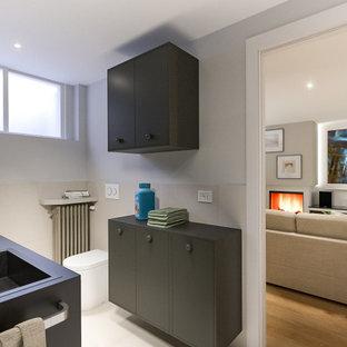 Idéer för ett litet minimalistiskt svart linjärt grovkök, med en nedsänkt diskho, släta luckor, svarta skåp, laminatbänkskiva, beige stänkskydd, stänkskydd i porslinskakel, grå väggar, klinkergolv i porslin, en tvättmaskin och torktumlare bredvid varandra och beiget golv