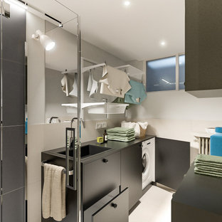Inspiration for a small scandinavian single-wall utility room in Milan with a drop-in sink, flat-panel cabinets, black cabinets, laminate benchtops, beige splashback, porcelain splashback, grey walls, porcelain floors, a side-by-side washer and dryer, beige floor, black benchtop and recessed.