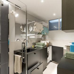 Exemple d'une petit buanderie linéaire scandinave multi-usage avec un évier posé, un placard à porte plane, des portes de placard noires, un plan de travail en stratifié, une crédence beige, une crédence en carreau de porcelaine, un mur gris, un sol en carrelage de porcelaine, des machines côte à côte, un sol beige, un plan de travail noir et un plafond décaissé.