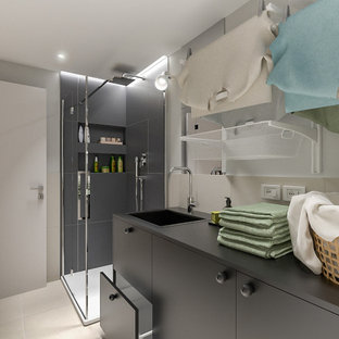 Photo of a small scandinavian single-wall utility room in Milan with a drop-in sink, flat-panel cabinets, black cabinets, laminate benchtops, beige splashback, porcelain splashback, grey walls, porcelain floors, a side-by-side washer and dryer, beige floor, black benchtop and recessed.