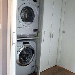 Immagine di una piccola sala lavanderia minimal con ante lisce, ante bianche, pareti grigie, pavimento in gres porcellanato, lavatrice e asciugatrice a colonna e pavimento marrone