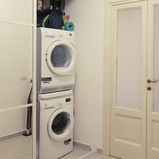Example of a small minimalist galley porcelain floor and beige floor laundry closet design in Milan with flat-panel cabinets, white cabinets, white walls and a concealed washer/dryer