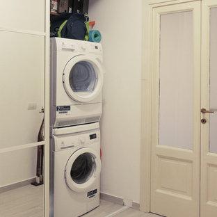 Cette image montre une petite buanderie parallèle minimaliste avec un placard, un placard à porte plane, des portes de placard blanches, un mur blanc, un sol en carrelage de porcelaine, des machines dissimulées et un sol beige.