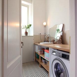 Immagine di una lavanderia multiuso scandinava di medie dimensioni con pareti bianche, pavimento con piastrelle in ceramica, pavimento multicolore, nessun'anta, top in legno, lavasciuga e ante in legno scuro