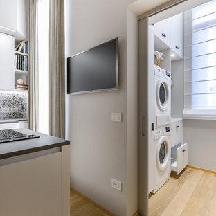 Ispirazione per una piccola sala lavanderia design con lavello da incasso, ante lisce, ante bianche, top in laminato, pareti grigie, pavimento in gres porcellanato, lavatrice e asciugatrice a colonna e top bianco