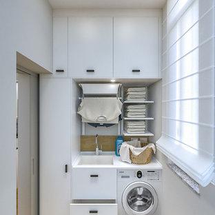 Immagine di una piccola sala lavanderia contemporanea con lavello a vasca singola, ante lisce, ante bianche, top in laminato, pareti grigie, pavimento in gres porcellanato, lavasciuga e top bianco