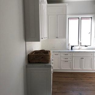 Idéer för en mycket stor klassisk grå u-formad tvättstuga, med en undermonterad diskho, luckor med upphöjd panel, vita skåp, bänkskiva i kvarts och grått stänkskydd