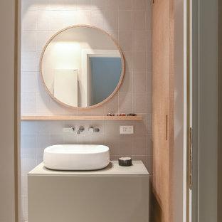 Exempel på en liten modern grå grått tvättstuga, med skåp i ljust trä, laminatbänkskiva, vita väggar, klinkergolv i porslin, tvättmaskin och torktumlare byggt in i ett skåp och grått golv