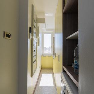Foto på en liten funkis gula linjär tvättstuga enbart för tvätt, med en nedsänkt diskho, släta luckor, gula skåp, bänkskiva i kvartsit, vita väggar, klinkergolv i porslin, en tvättpelare och grått golv