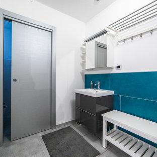 Idee per una grande lavanderia multiuso minimal con lavello a vasca singola, ante lisce, ante grigie, top in superficie solida, pareti bianche, pavimento in gres porcellanato, lavatrice e asciugatrice affiancate, pavimento grigio, top bianco e travi a vista