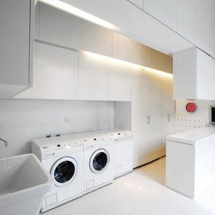 Immagine di una grande sala lavanderia design con lavello a vasca singola, ante lisce, ante bianche, pareti bianche e pavimento in gres porcellanato