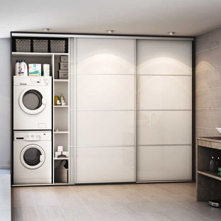 Inspiration for a mid-sized mediterranean single-wall ceramic floor and beige floor dedicated laundry room remodel in Florence with an undermount sink, glass-front cabinets, white cabinets, glass countertops, beige walls and a stacked washer/dryer