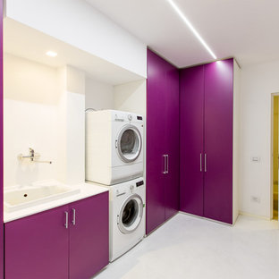 Trendy single-wall dedicated laundry room photo in Other with a drop-in sink, flat-panel cabinets, white walls and a stacked washer/dryer