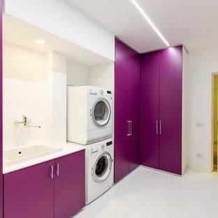 Réalisation d'une buanderie linéaire design dédiée avec un évier posé, un placard à porte plane, un mur blanc et des machines superposées.