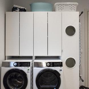 Exemple d'une buanderie linéaire moderne multi-usage et de taille moyenne avec un évier 2 bacs, un placard à porte plane, des portes de placard blanches, un plan de travail en bois, un mur beige, un sol en carrelage de porcelaine, des machines côte à côte, un sol gris et un plan de travail blanc.